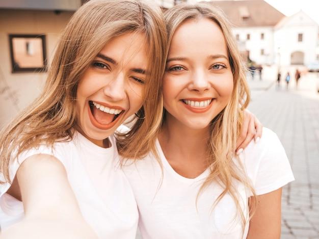 Zwei junge lächelnde blonde frauen des hippies im weißen t-shirt des sommers kleidet. mädchen, die selfie selbstporträtfotos auf smartphone machen.