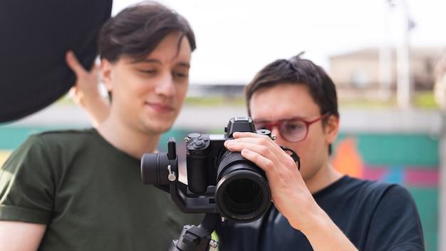 Zwei junge lächelnde fotografen, die die kamera auf einem stativ bei der fotosession betrachten