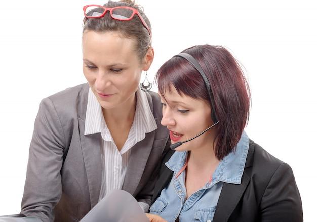 Zwei junge lächelnde frauen, die zusammen mit notizbuch arbeiten