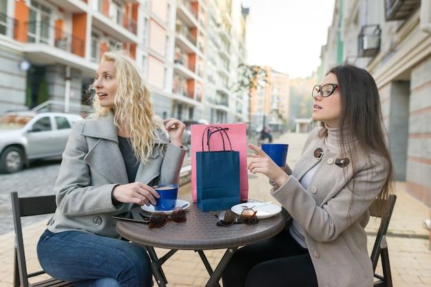 Zwei junge lächelnde frauen in einem café im freien