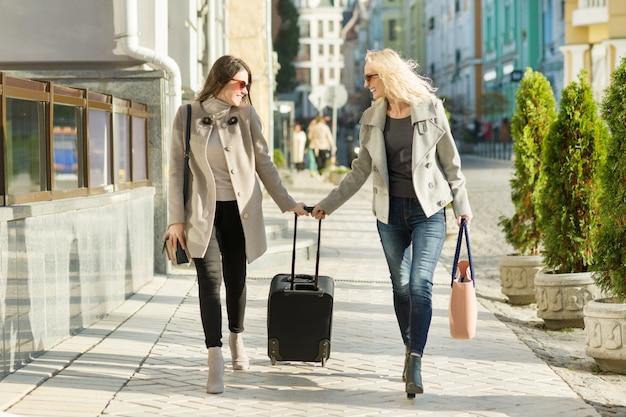 Zwei junge lächelnde frauen mit einem koffer