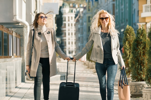 Zwei junge lächelnde frauen mit koffer