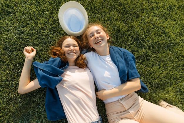 Zwei junge lächelnde freundinnen liegen umarmen
