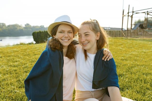 Zwei junge lächelnde freundinnen sitzen umarmen