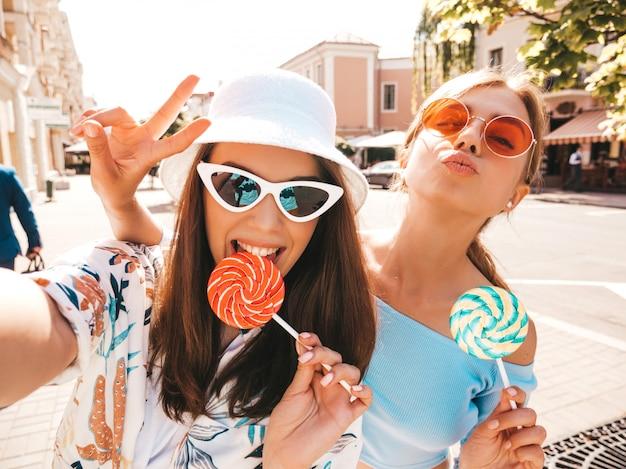 Zwei junge lächelnde hippie-frauen in der zufälligen sommerkleidung.