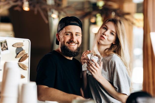 Zwei junge lächelnde menschen. gekleidet in lässigem outfit, stehen nebeneinander und lächeln in einem gemütlichen café in die kamera. .
