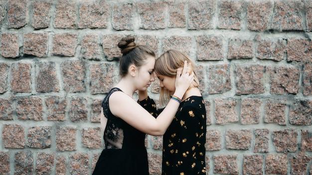 Zwei junge lesbenmädchen, die draußen umarmen.