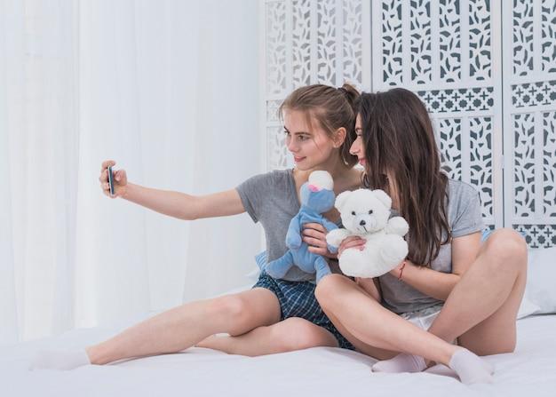 Zwei junge lesbische paare, die auf dem bett nimmt selfie am handy sitzen