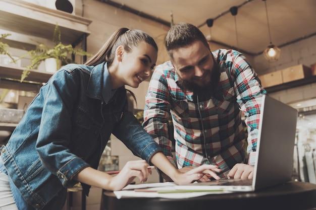 Zwei junge leute, die an einem laptop im café arbeiten.