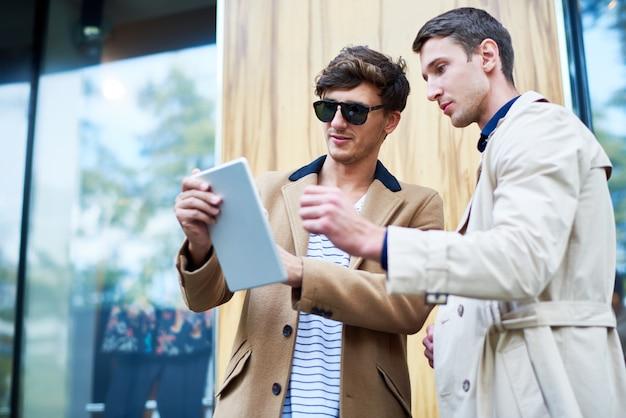 Zwei junge leute, die digitales tablett in straße verwenden