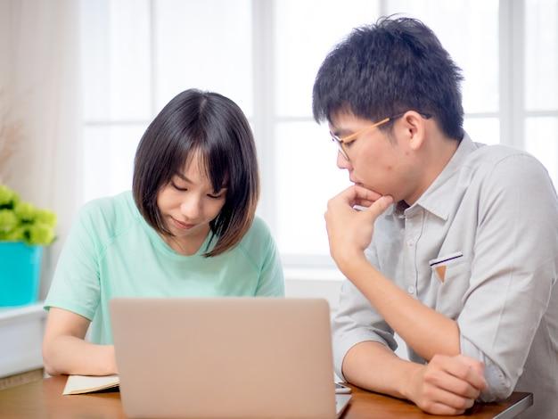 Zwei junge leute diskutieren vor laptop