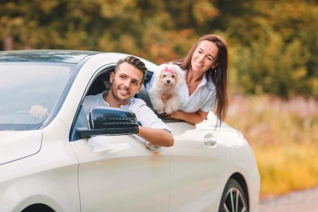 Zwei junge leute genießen sommerferien. glückliche paartouristen schauen vom auto aus