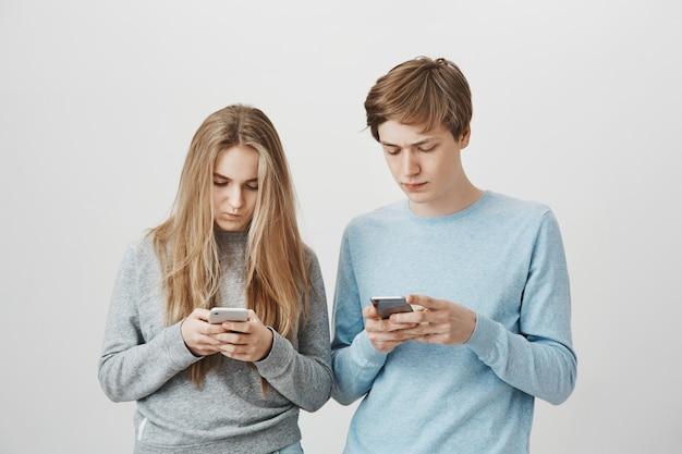Zwei junge leute mit smartphone. mädchen und kerl sms mit ernsten gesichtern