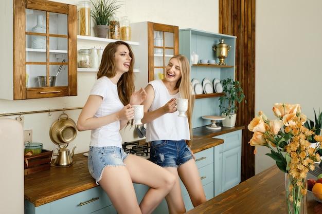 Zwei junge lustige frauen, die geschichten erzählen und in der küche lachen