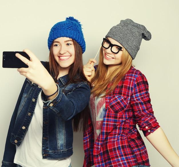 Zwei junge lustige frauen, die selfie mit handy machen