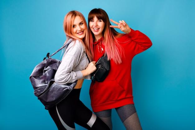 Zwei junge lustige hübsche hipster-frauen, die sportliche helle lässige outfits tragen, lächelnd posierend, bereit für crossfit und fitness