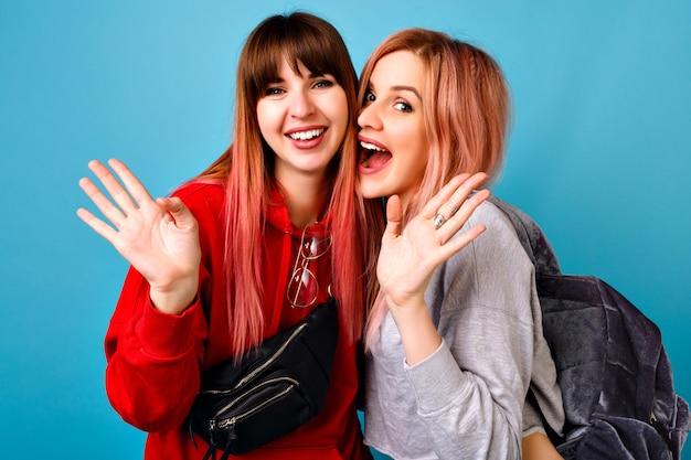 Zwei junge lustige hübsche hipster-frauen, die sportliche helle lässige outfits tragen, schreiend lächeln und hallo zu ihnen sagen, blaue wand