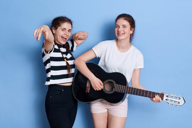 Zwei junge lustige mädchen der brünette tanzen singen und spielen akustische gitarre, während sie isoliert über dem blauen raum stehen