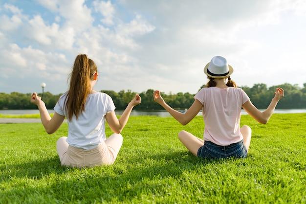 Zwei junge mädchen, die die yogahaltung im freien tun