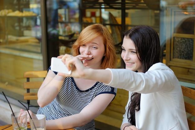 Zwei junge mädchen, die ein selbstporträt (selfie) mit intelligentem telefon nehmen