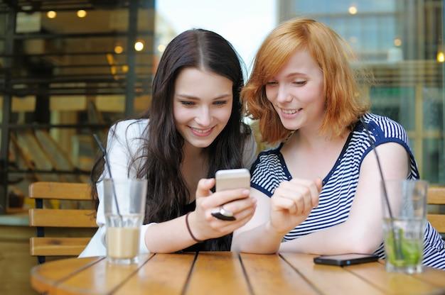 Zwei junge mädchen, die intelligentes telefon am freiencafé verwenden