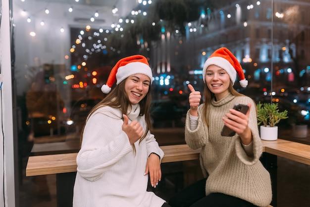 Zwei junge mädchen, die smartphone im café benutzen