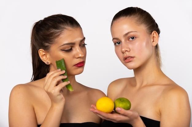 Zwei junge mädchen, eine braunhaarige frau mit früchten in der hand, eine brünette mit aloe vero. auf weiß isoliert. spa und gesundes lebensmittelkonzept. hochwertiges foto