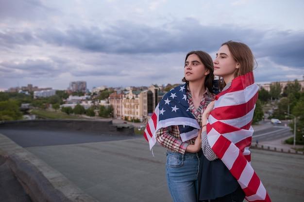 Zwei junge mädchen eingewickelt in amerikanische flagge. glückliche patriotische studenten auf dem dach. teenager-schwestern im urlaub feiern den unabhängigkeitstag