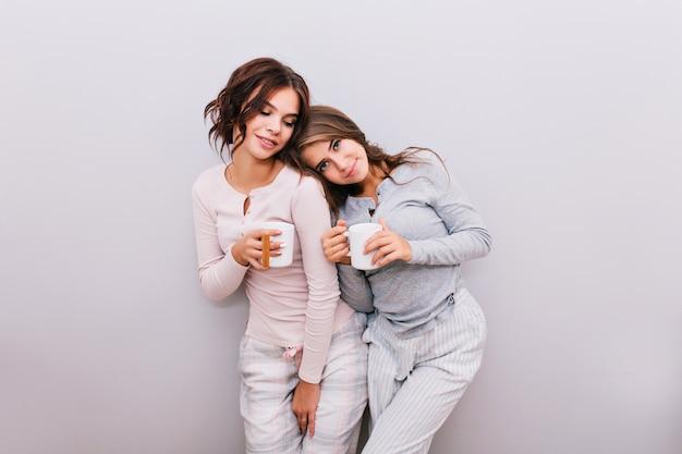 Zwei junge mädchen im pyjama mit tassen auf grauer wand. mädchen mit langen haaren lehnen kopf auf schulter des mädchens mit lockigem haar. sie sehen genossen aus.