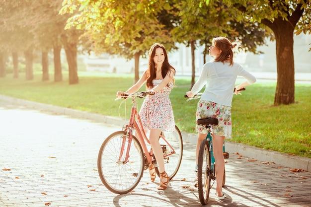 Zwei junge mädchen mit fahrrädern im park