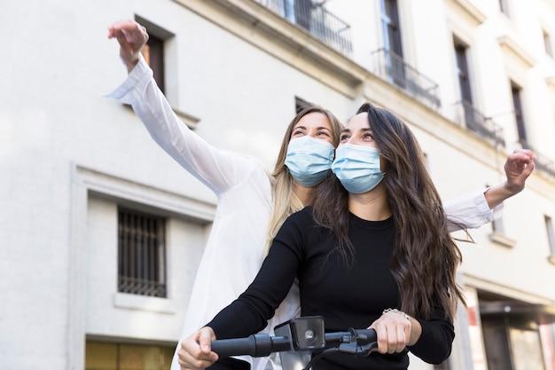 Zwei junge mädchen mit medizinischen masken, die während der covid-19-periode spaß im urlaub haben.