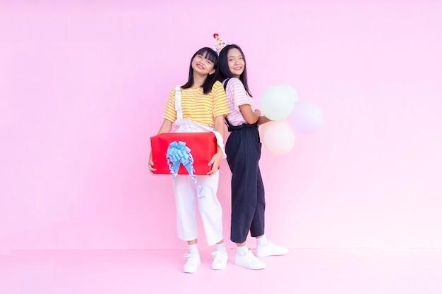 Zwei junge mädchen mit rotem geschenkboxballon auf rosa hintergrund.