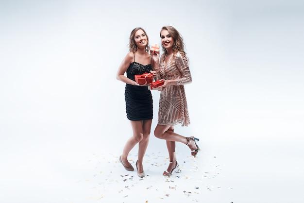Zwei junge mädchen mit roten geschenken in den händen getrennt auf weiß