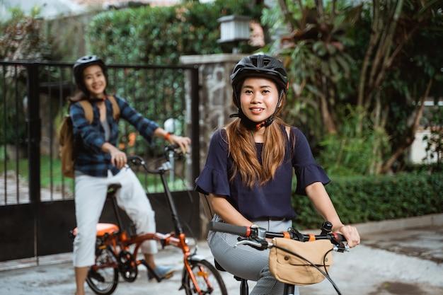 Zwei junge mädchen sind bereit, mit dem faltrad zur schule zu gehen