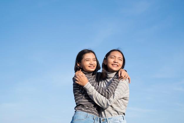 Zwei junge mädchen tragen jeans stehend, umarmend und lächelnd mit blauem himmelhintergrund.