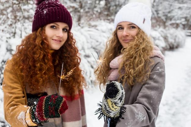 Zwei junge mädchenschwestern halten wunderkerzen