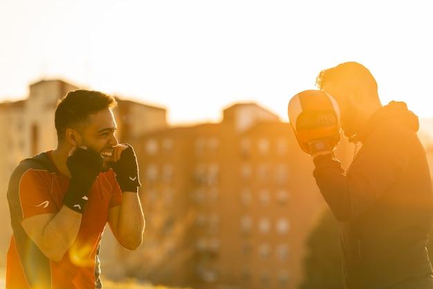 Zwei junge männer, die draußen boxen