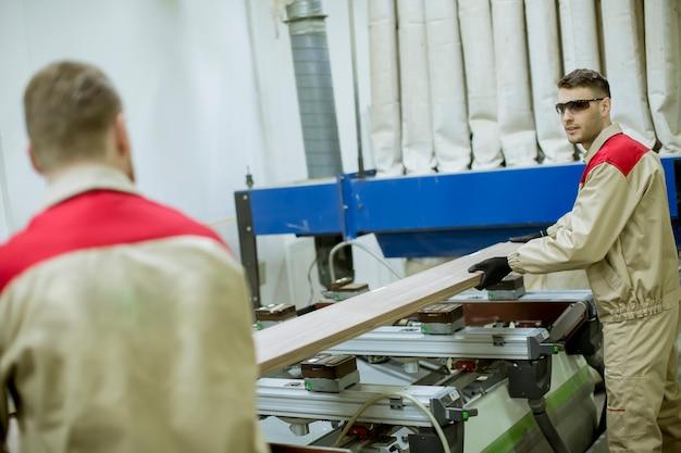 Zwei junge männer, die in der möbelfabrik arbeiten
