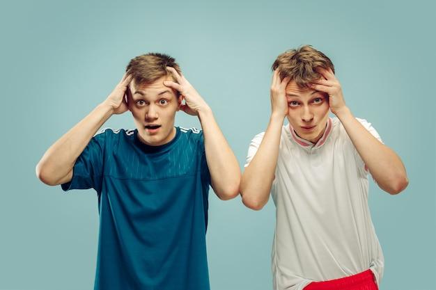 Zwei junge männer, die in der sportbekleidung stehen, isoliert. fans von sport, fußball oder fußballverein oder -mannschaft. halbporträt der freunde. konzept menschlicher emotionen, gesichtsausdruck.