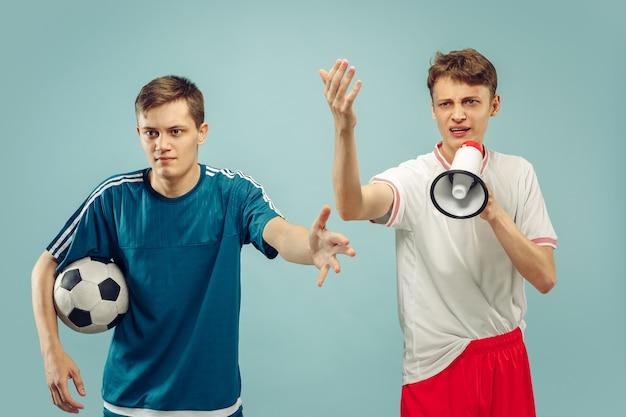 Zwei junge männer, die in der sportkleidung stehen, lokalisiert auf blau