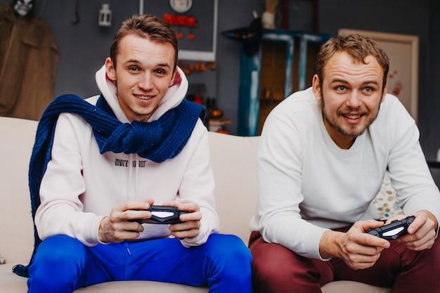 Zwei junge männer, die videospiele spielen
