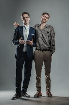 Zwei junge männer gleichen alters, die unterschiedlich gekleidet sind und zusammen posieren.