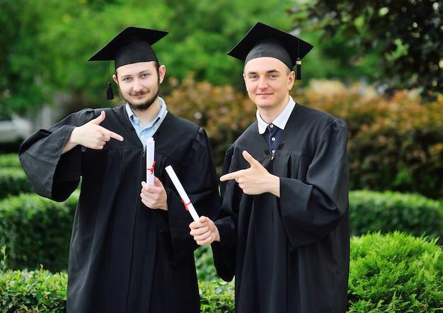 Zwei junge männer-hochschulabsolventen in roben und eckigen hüten freuen sich über ein diplom.