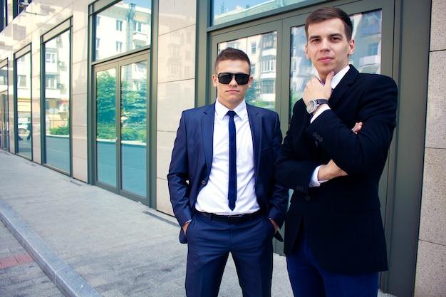Zwei junge männer in anzügen vor dem hintergrund eines geschäftszentrums