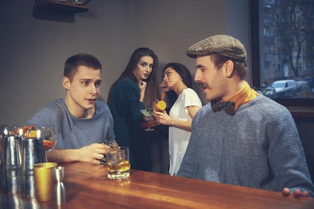 Zwei junge männer in freizeitkleidung sprechen beim sitzen am bartheke in der kneipe