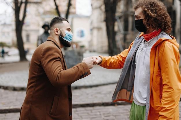 Zwei junge männer in medizinischen schutzmasken, die mit fauststoß draußen grüßen. konzept der quarantänemaßnahme und der sozialen distanz.