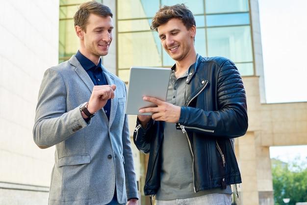 Zwei junge männer mit digitalem tablet
