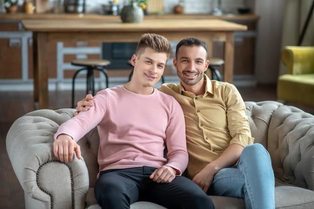 Zwei junge männer sitzen auf dem sofa und sehen glücklich aus