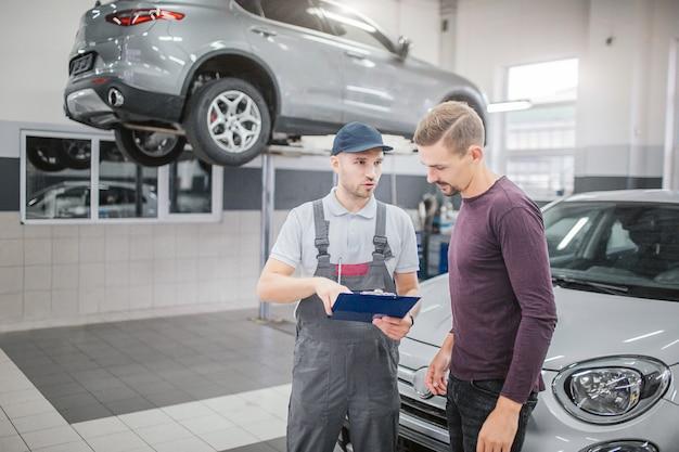 Zwei junge männer stehen in der garage am auto und unterhalten sich. mann in uniform hält dokumente und zeigt darauf. er sieht den bärtigen mann an. blonder mann schaut auf papiere. er ist besitzer eines autos.