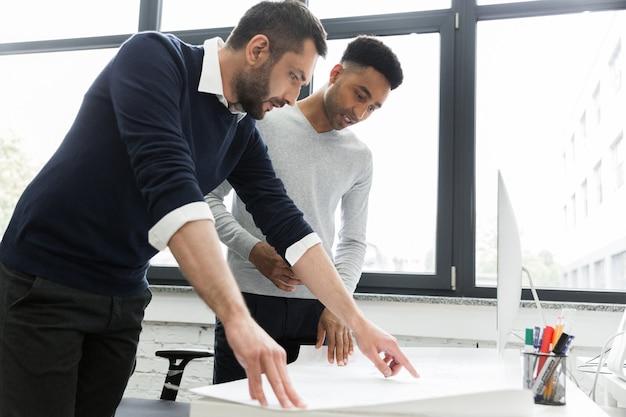 Zwei junge männliche büroangestellte, die auf eine karte zeigen